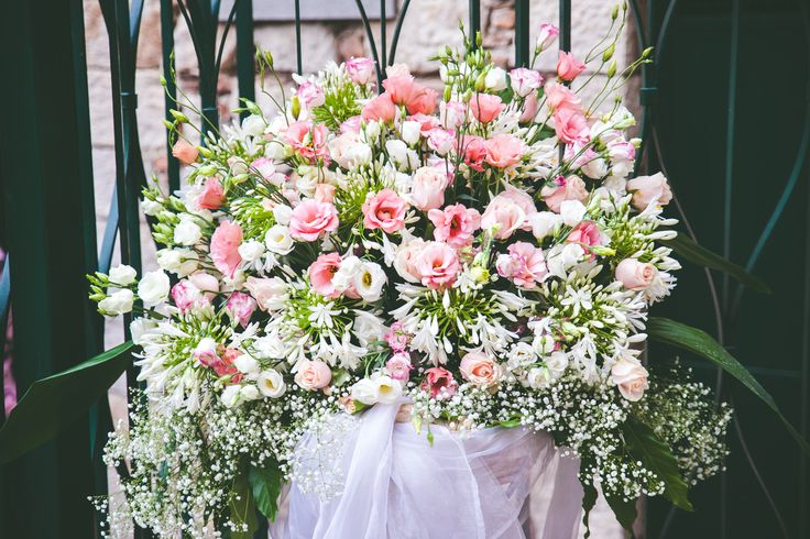 Wedding ceremony fresh flowers arrangement. White, cream and pink shades, lisianthus, roses, agapantus.