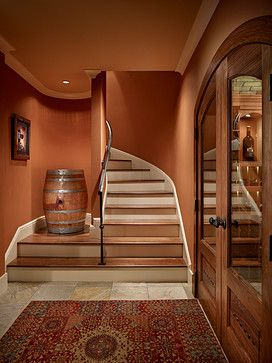 Hallway to Wine Cellar with Burnt Orange Walls (Sherwin Williams SW 6634, Copper Harbor) and Rug - Gelotte Hommas Architecture, gelottehommas.com