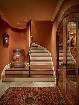 Hallway to Wine Cellar with Burnt Orange Walls (Sherwin Williams SW 6634, Copper Harbor) and Rug - Gelotte Hommas Architecture, gelottehommas.com
