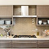 Neutral kitchen backsplash Neutral Drama  Paired with frameless cabinetry and streamlined cabinet pulls, this glass backsplash looks sophisticated and contemporary. The champagne-color glass tiles, gray-stained alder cabinets, and creamy marble countertops maintain a neutral color palette, but their varied shades ensure the look is anything but boring. The tile's glossy finish mirrors the sheen of stainless-steel appliances and reflects light and views.