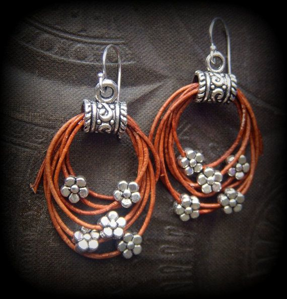 Are these fun or what!!! Rustic Tibetan silver tubes hold layers of aged tan leather with silver flowers, finished off with sterling silver ear wires.