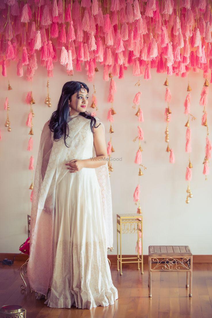Mehendi Decor - Pink Tassle Decoe and the Bride wearing a White Light Lehenga | WedMeGood #wedmegood #decor #pinkdecor #tassleddecor #hangingdecor #lightlehenga #white #pink