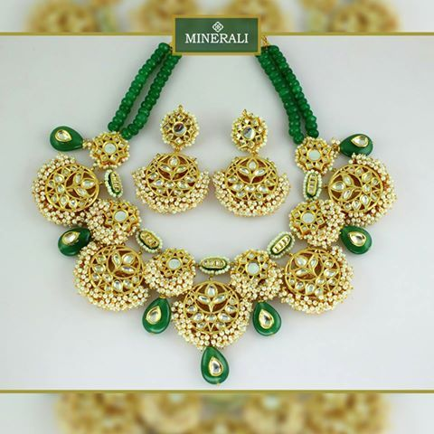 Kundans set in a gold frame with tiny pearls and green beads, this beautiful set by Just Jewellery will look no less than a piece of art on you. Available at Minerali.