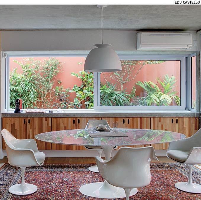 A copa possui uma janela que avança no recuo lateral da casa. O caixilho de alumínio forma uma caixa embaixo da laje do teto e sobre a laje em balanço, que funciona como aparador. Projeto do arquiteto André Vainer.