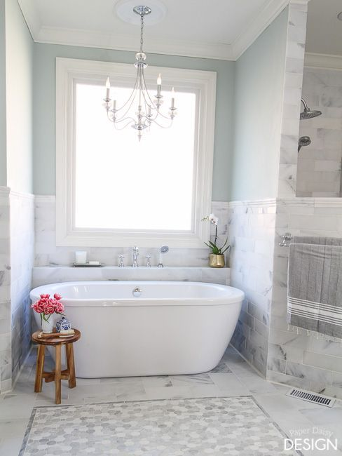 The final reveal of a DIY marble master bathroom featuring a blunt herringbone floor, mosaic tile wall, mosaic tile shower floor in a walk-in, doorless, glass less shower. The feature of the room is a budget friendly freestanding tub with economical solution to traditional floor mounted tub fillers.