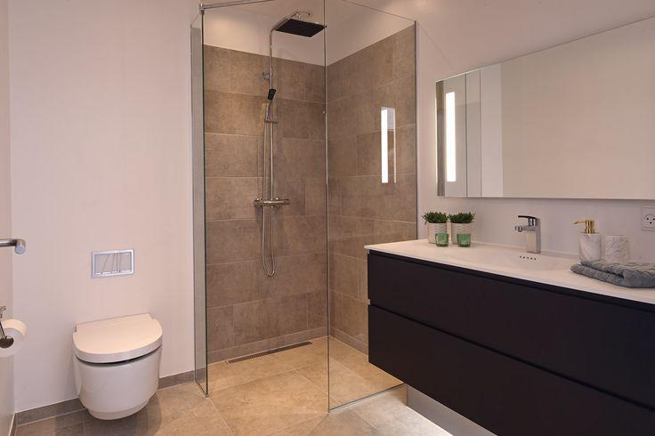 Lækkert badeværelse med skjult cisterne, brusevægge i glas og hvide marmorline bordplader med formstøbte vaske.