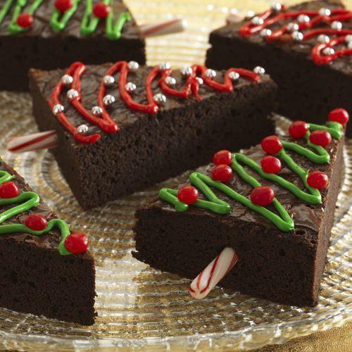 Bak een grote plak brownie en snijdt in driehoeken. Decoreer met groen, rood en zilver. Gebruik (halve) zuurstokjes als stam. Foto e...