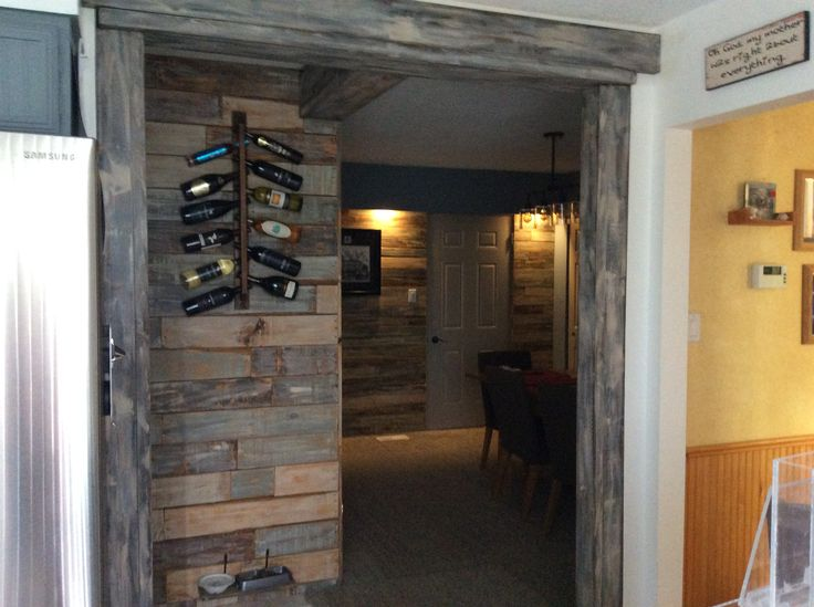Updated dining room with pallet board accent walls and faux wood beams in entry.