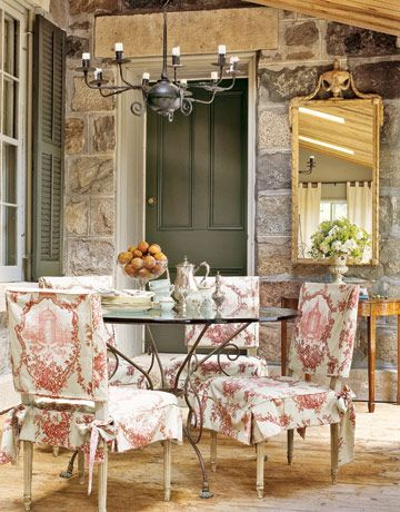 In the solarium, the shutters and door frame were painted a gentle green to complement the stones' neutral palette, while dining chairs are slip-covered in rasberry toile.   - CountryLiving.com
