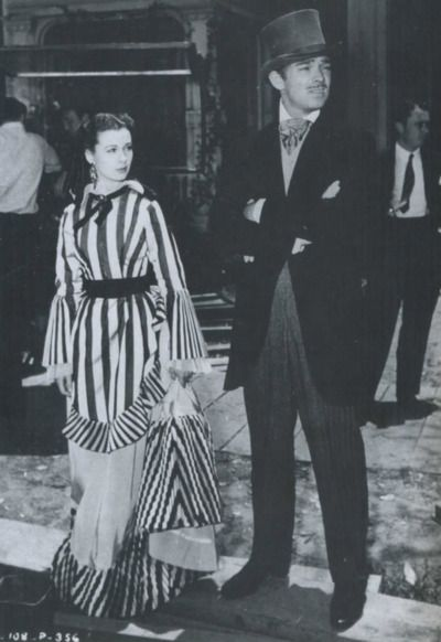 On the set of Gone With The Wind. Vivien Leigh and Clark Gable ready for the scene strolling Bonnie in Atlanta.