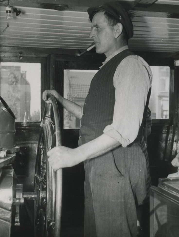 Een Nederlandse binnenschipper aan het stuurwiel van zijn schip. Nederland, 1941.