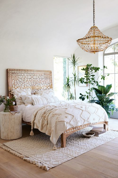 A grand decorative headboard and boho accents in an otherwise neutral room make for a strong summer boho statement