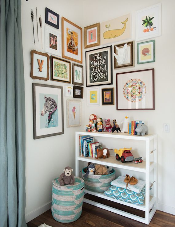 Adorable nursery features an eclectic art gallery wall wrapping around the corner over a Serena and Lily Cabot Bookshelf lined with toys and woven blue and gray baskets beside the window which is dressed in slate blue drapes.