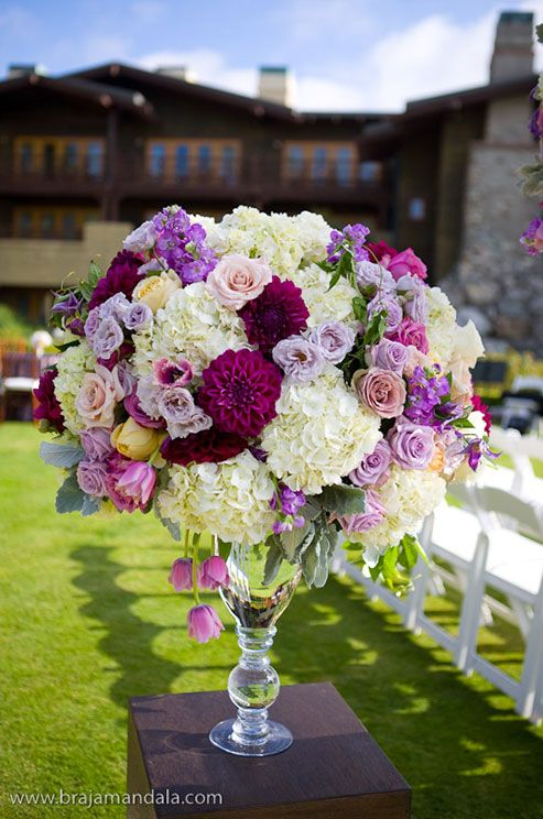 Fresh hydrangeas, roses, vibrant dahlias, tupips and carnations are stunning against the green grass and dark hues of the lodge.