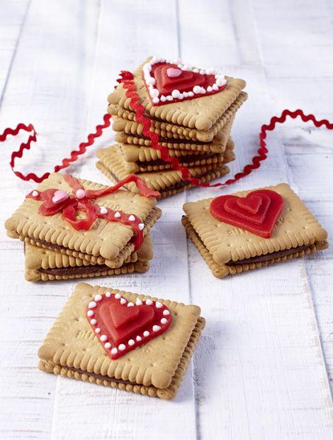 Zutaten für 4 Stück:1 Pck. Keks'n Cream Choco von Leibniz. Zum Verzieren: Dekor Marzipan (rot) oder Marzipan Rohmasse, etwas Puderzucker, rote Speisefarbe. Zum Garnieren: weiße Zuckerschrift, Dekorschmuck.  Zubereitung: Dekor Marzipan (oder Marzipan Rohmasse mit etwas Puderzucker verkneten, mit roter Speisefarbe einfärben) dünn ausrollen, mit Herzausstechformen in unterschiedlichen Größen Herzen ausstechen. Mit etwas Zuckerschrift die Herzen auf die Keks'n Cream Kekse schichten. Nach…