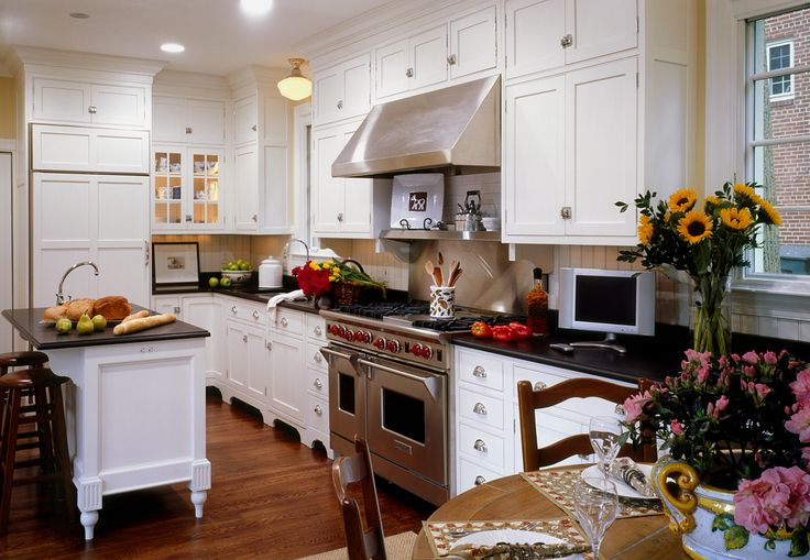 White shaker style cabinets stacked to the ceiling flank a for Double kitchen cabinets