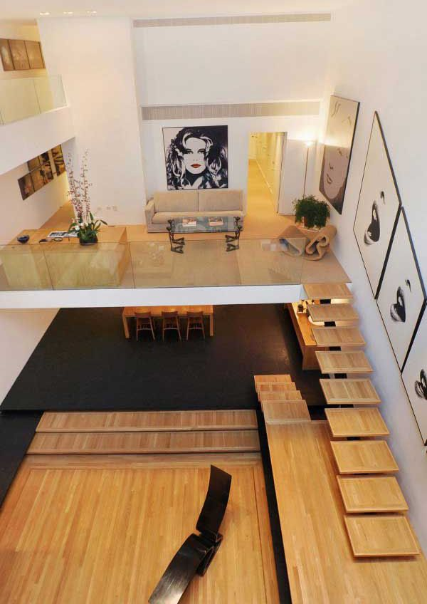 Balancing dark floors and a sunken white oak platform, this modern New York Urban Retreat by Paul Rudolph displays a floating staircase leading up to the living area mezzanine.