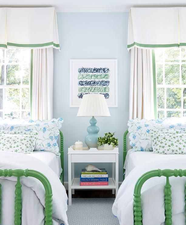 Feel right at home in this beautiful blue and green shared girls' bedroom fitted with green Jenny Lind Beds placed on a blue rug between a Oomph Edgartown Side Table with Drawer lit by a blue three gourd lamp placed in front of a framed print.
