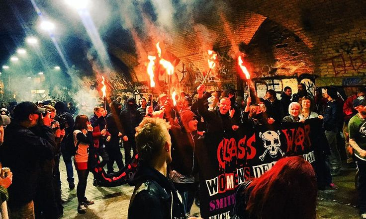 "Hundreds of protesters attacked a cereal cafe in east London on Saturday night, daubing the word ""scum"" on the shop window and setting fire to an effigy of a police officer."