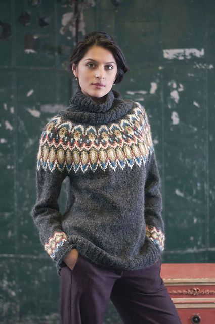 Gunderson alludes to the fine angora halo of traditional Bohus sweaters with this roomy turtleneck pullover knit in Universal Yarn's brushed-mohair-blend Amphora. Worked seamlessly from the top down, it sports Bohus-like colorwork on the yoke and sleeves; the five shades create a vibrant counterpoint to the charcoal background. Double ribbing trims the cuffs, hem and collar, which is knit separately and sewn to the neckline in finishing.