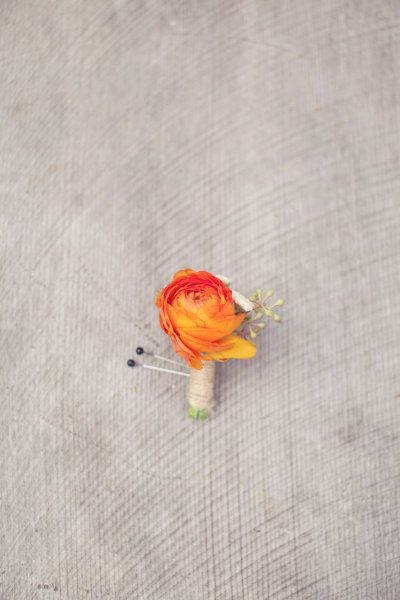 tiny orange ranunculus boutonniere packs a punch of color