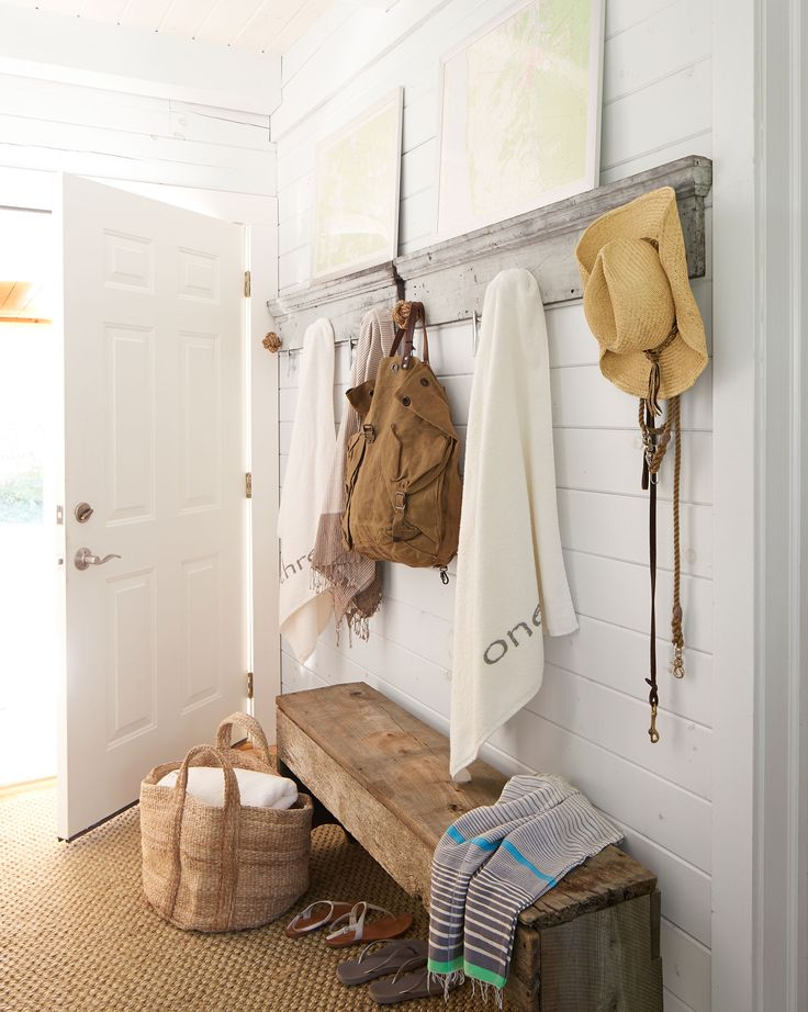 julie turned the back hall into a mudroom outfitted with salvaged door frames with rope balls for hooks and a bench crafted from reclaimed barn wood