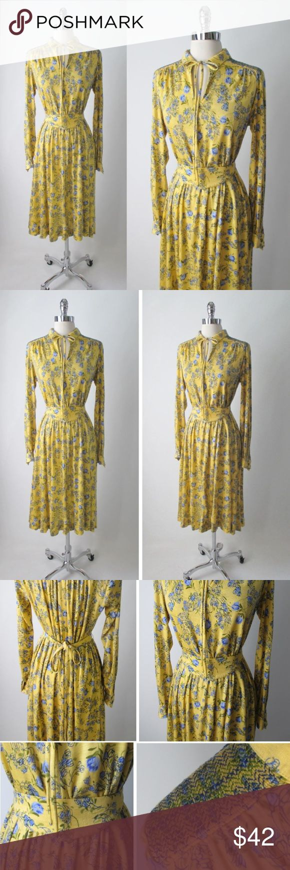 Vintage 70's Yellow Flower Keyhole Day Tent Dress 1970's Yellow with pretty blue and green floral. A line style cut that wears like a tent dress without the belt Keyhole tie at the neck. Smocked shoulders + Button cuffs. Matching belted waist with a soft fullness to the skirt. Soft jersey style cotton + Tricoville • Made in England • Marked USA 10 Underarm: 47 Waist: 50 Hips: 66  Shoulder to waist: 16  inches Waist to hem: 28 inches Sleeve length: 24  I can't find any tears, stains, fade or…