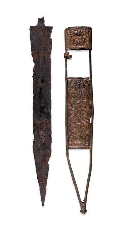 "The Fulham Sword  Roman Britain, 1st century AD  The British Museum  ""This is the characteristic sword of the Roman legionary at this period. Only the handle, and the wooden or leather lining of the sheath are missing. Metallographic examination of the iron blade has shown that the cutting edges have been hardened.  The maker has decorated the bronze scabbard plate with embossed motifs. These include the popular Roman motif of the she-wolf suckling the twins Romulus and Remus, the legendary…"