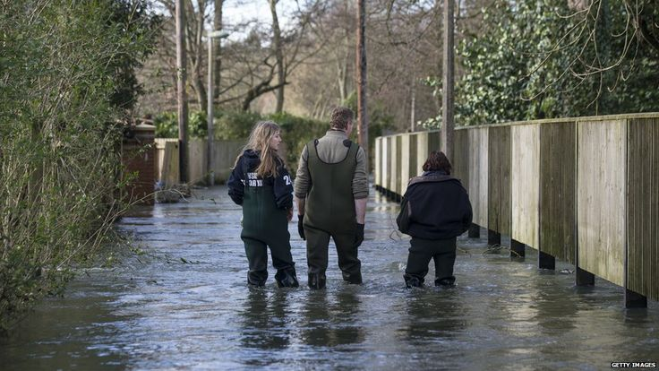 Residents walk along a flooded street in Henley-on-Thames. Areas across England and Wales remain badly affected by the flooding, with more rain expected on Monday.
