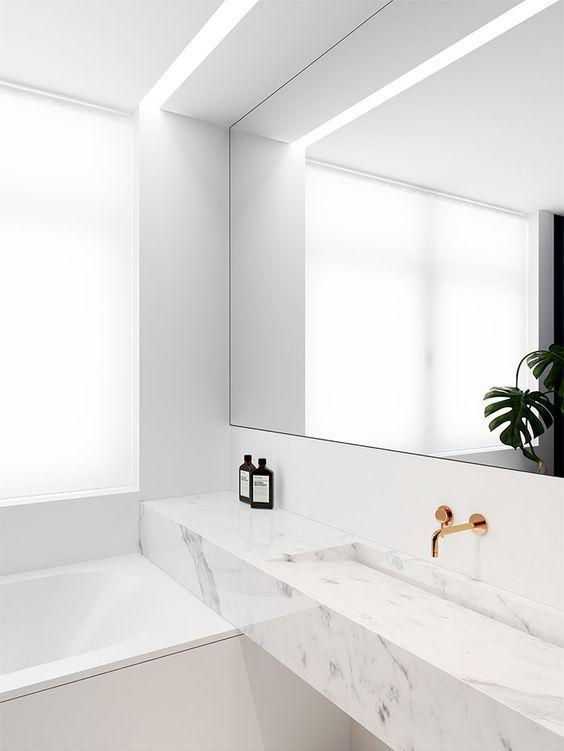 Banheiro com pia de mármore  contínua sobre a banheira.