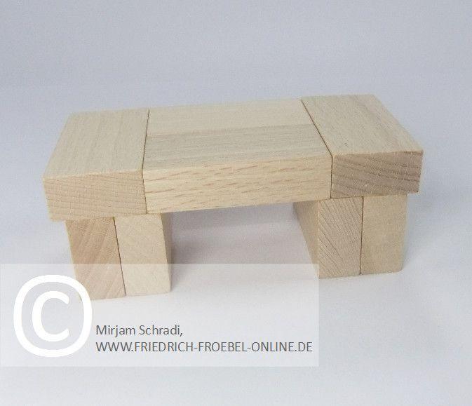 kleiner Tisch aus Holzbausteinen natur mit Spielgaben nach Froebel (Spielgabe 4)