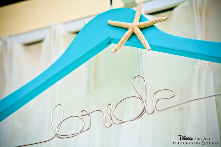 """Bright blue """"bride"""" hanger embellished with a starfish for the wedding dress"""