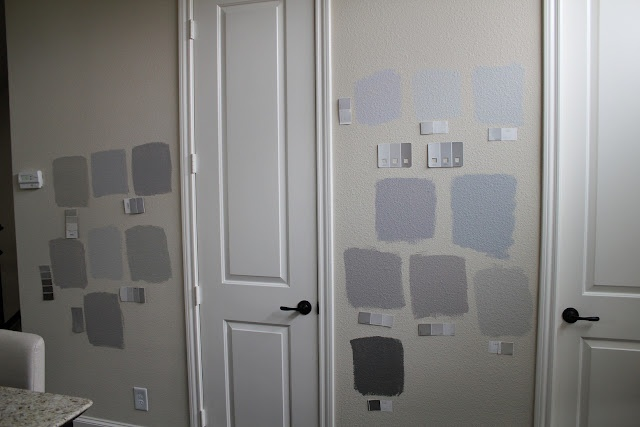 Gray paint samples on wall with list of names - Benjamin Moore & Sherwin Williams