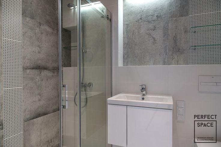 Aranżacja łazienki z prysznicem z przesuwanymi szklanymi drzwiami. Łazienka w minimalistycznym stylu z płytkami imitującymi beton oraz białymi meblami.