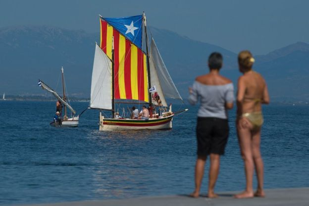 A sail boat carrying an Estelada Catalan independence flag sails off a beach near Girona, 10 September