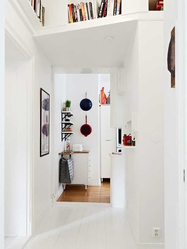 A white Swedish apartment with white cabinets wooden benchtops, flashes of colour elsewhere