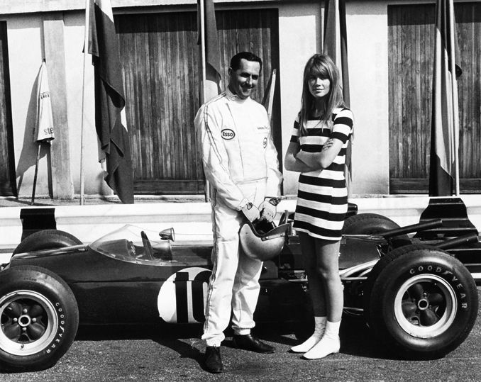 Francoise Hardy with Formula One racing legend (Sir) Jack Brabham, three-time World Champion, during the filming of Grand Prix, 1966. Brabham was the first driver in history to be knighted for his services to motorsport, and the only Formula One driver to have won a world title in a car of his own construction – the BT19 – which he drove to victory in 1966.