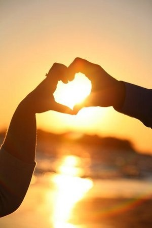 Couple's hands heart the sun in the horizon