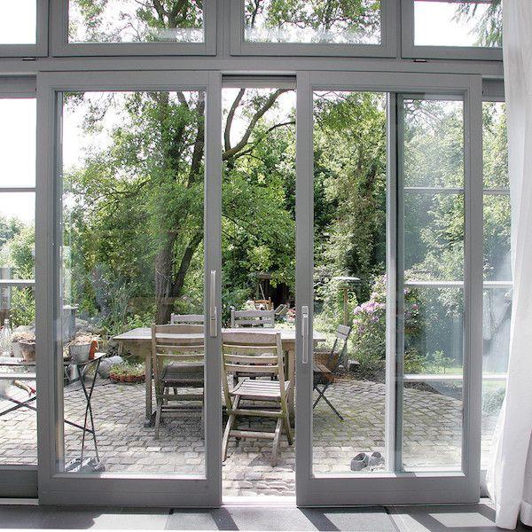 Ein Schritt in den verwunschenen Garten: zweiflügelige, graue Hebeschiebetür als Tor zur Terrasse | Sorpetaler Fensterbau