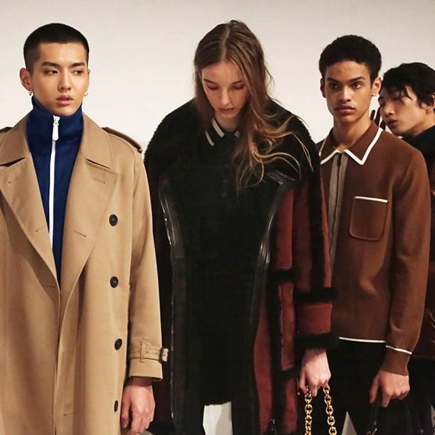 Models line up backstage at the Burberry 2016 runway show in oversize outerwear – The Trench Coat is worn over a blue tracksuit jacket and shearling coats come panelled in black and dark red