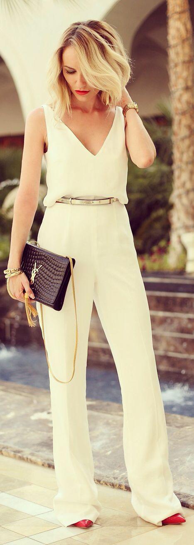 Ella está vestida con un jumpsuit blanco, unos tacones rojos, un reloj de oro, una bolsa negra, unas pulseras de oro.  (Melissa)