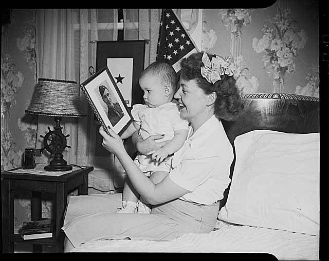 Showing a baby it's father's photo on Father's Day (1941)