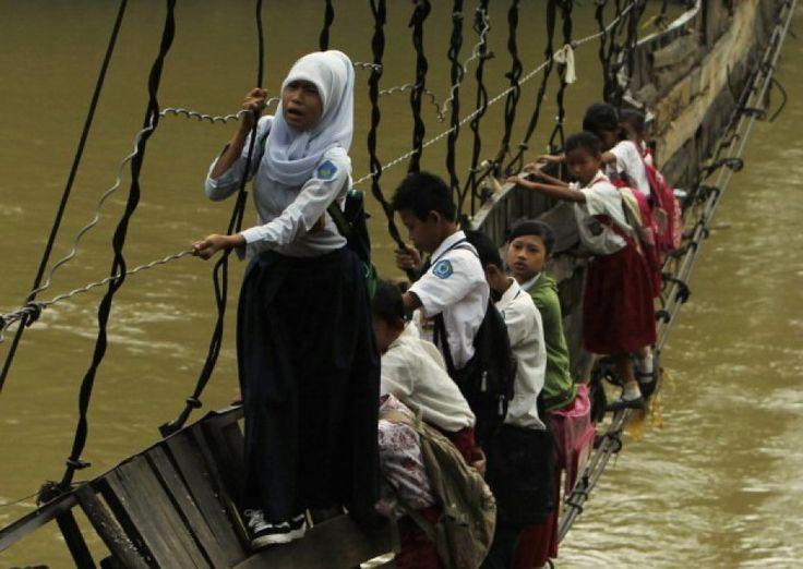Indonesia, per raggiungere il villaggio di Sanghiang Tanjung, dove si trova la loro scuola, questi bambini erano costretti ad attraversare il fiume Ciberang tutti i giorni della settimana, con il rischio di gravi incidenti: 30 minuti aggrappati a quello che resta del ponte danneggiato. Dopo la diffusione di questa fotografia, una delle aziende edilizie indonesiane più importanti si è preoccupata di costruire un ponte in ferro più sicuro