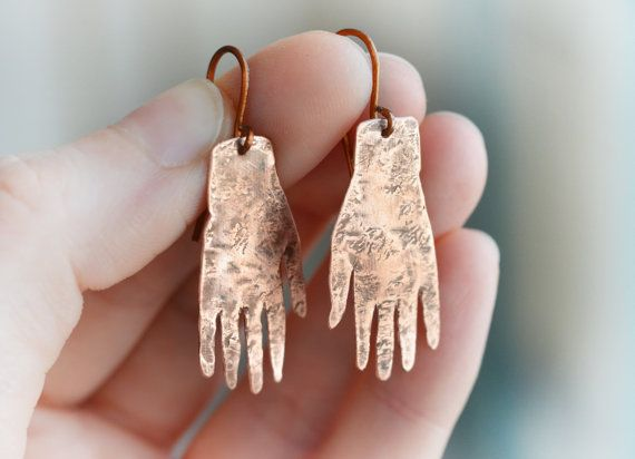 This is a copper earring made in my studio.  This pair was inspired by the earrings of the painter Frida Kahlo, who was best known for her brave self portraits. The white hand earrings were one of her favourite earrings to wear and can be seen on some of her work.  I made these earrings out of solid copper sheet with copper earwires (feel free to change the earwires to one of your preferance, if you would like another type). The copper has some texture for a bit of fun and a bit of patina…