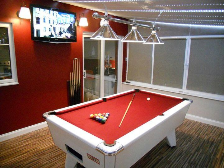 Red and white supreme winner 7 foot pool table Looks like chalk paint on back wahll.
