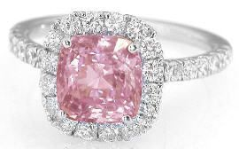 This natural padparadscha  pink sapphire and diamond halo ring will absolutely take her breath away! It features an eye catching pastel peachy pink unheated padparadscha sapphire in a cushion cut. This sapphire is so unbelievably rare and special. Only padparadscha sapphires have that delicate and desirable combination of peach and pink, and this beautiful sapphire is also completely natural and unheated. Found at MyJewelrySource.