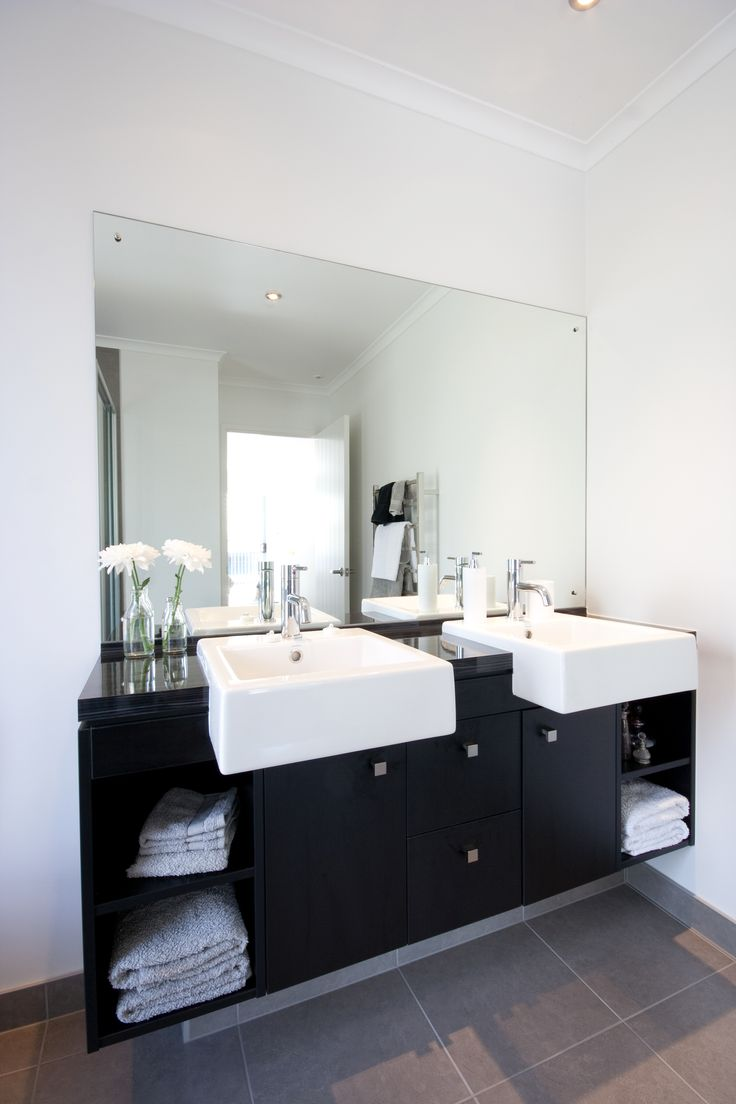 Twin basins feature in this ensuite bathroom, with both open and closed storage options.