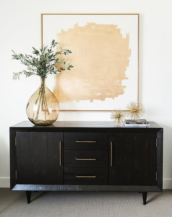 Chic bedroom features a gold abstract art placed over a black credenza adorned with brass pulls topped with an amber glass vase.