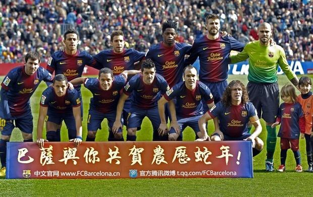 """O Barça aproveitou a exposição no outro lado do mundo e fez uma homenagem ao Ano Novo chinês, celebrado neste domingo: crianças chinesas entraram em campo ao lado dos jogadores usando camisas com mensagem de """"Feliz Ano Novo"""".  (Foto: EFE)"""