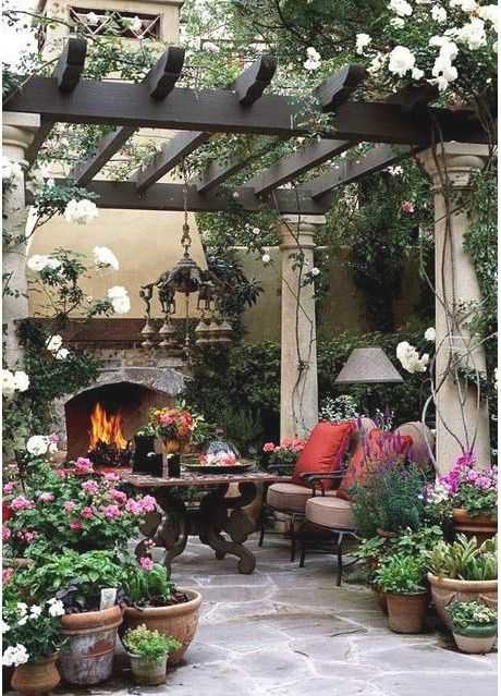 Beautiful patio, love the fireplace...all the potted plants & the fireplace & pergola with the columns!